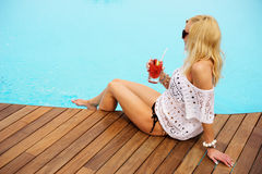 Young blonde woman relaxing at the pool Stock Images