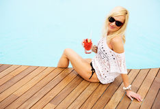 Young blonde woman relaxing at the pool Stock Photo