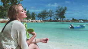 Young blonde woman relaxing on a tropical beach. Pretty girl sitting on a beach and enjoying a beautiful view of the open sea stock video