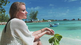 Young blonde woman relaxing on a tropical beach. Pretty girl sitting on a beach and enjoying a beautiful view of the open sea stock footage