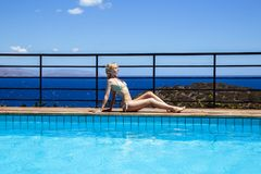 Young blonde woman resting near pool in a summer day Royalty Free Stock Images