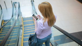 Young blonde woman riding on escalator in underground and using smart phone. stock footage