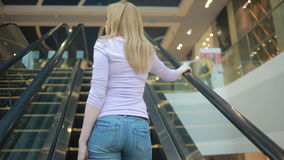 Young blonde woman riding on escalator in underground and using smart phone. Urban lifestyle, keeping in touch every minute stock footage