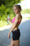 Young blonde woman runner holds blue bottle Stock Image