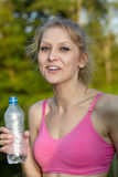 Young blonde woman runner holds blue bottle Royalty Free Stock Photography