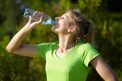 Young blonde woman runner holds blue bottle Stock Images
