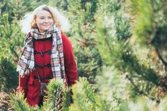 Young blonde woman selecting Christmas tree on the market before New Year celebration