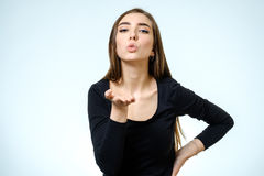 Young blonde woman sending an air kiss to the camera Royalty Free Stock Images