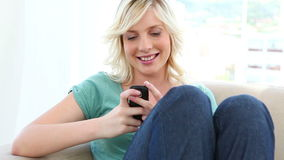 Young blonde woman sending text message stock video