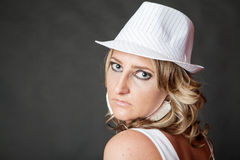 Young blonde woman with serious face wearing white hat Royalty Free Stock Image