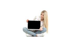 Young blonde woman showing blank laptop computer screen sitting. On the floor with crossed legs. Close-up screen Royalty Free Stock Images