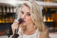 Young blonde woman singing while looking at camera Stock Images