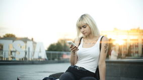 Young blonde woman sits on a bench uses smartphone glare of sunset light reflected from the glass stock footage