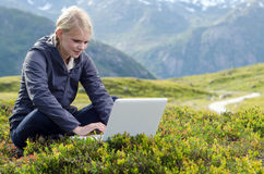 Young blonde woman sits with laptop in meadow Stock Photos