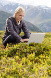 Young blonde woman sits with laptop in meadow Royalty Free Stock Image