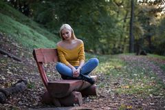 Young blonde woman sitting alone on a wooden bench in the forest, sad and lonely stock image