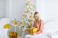 Young blonde woman sitting on the bed, opens gift box. Christmas morning. Young blonde woman sitting on the bed, opens gift box. Portrait against the background Royalty Free Stock Image
