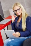 Young blonde woman talking on mobilephone. Young blonde woman sitting at desk, using mobilephone and tablet computer, smiling, talking Royalty Free Stock Images