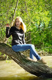 Young blonde woman sitting on dried-up tree Royalty Free Stock Images