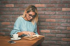 Young blonde woman sitting enjoy reading book at cafe. Vintage filter toned. Royalty Free Stock Photos