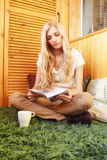 Young blonde woman sitting on green carpet with book Royalty Free Stock Photos