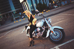 Young blonde woman sitting on a motorcycle on the background of Stock Photos