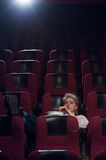 Young blonde woman sitting in movie theater stock photo