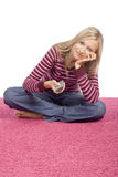 Young blonde woman sitting on the pink carpet with remote contro Royalty Free Stock Photos