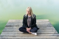 Young blonde woman sitting in pose of lotos on pier in autumn on background of lake.  Royalty Free Stock Images