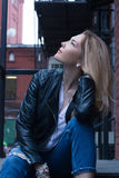 Young blonde woman sitting on stairs. Casual style. Urban background Stock Photo