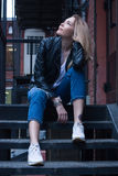 Young blonde woman sitting on stairs. Casual style. Urban background Stock Image
