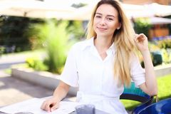 Young blonde woman sitting at street cafe outside. stock images