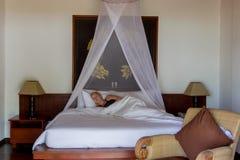 Young blonde woman sleeping in luxury bedroom villa stock photo