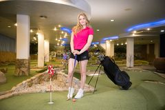 A young blonde woman in small black shorts standing in golf club near the stick bag. Mid shot stock photos