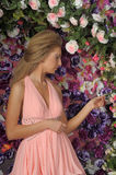 Young blonde woman in a smart pink dress Stock Photo