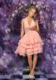 Young blonde woman in a smart pink dress Stock Photography