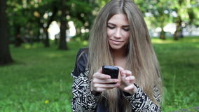 Young blonde woman with smartphone stock footage