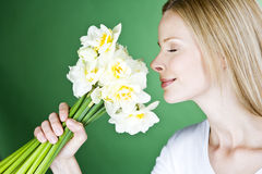A young blonde woman smelling a bunch of daffodils, side view Royalty Free Stock Image