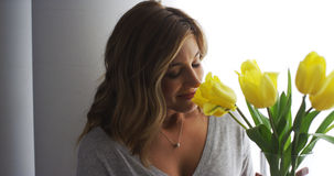 Young blonde woman smelling yellow tulips Stock Image