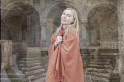 Young blonde woman smiling with  with castle in background. Young blonde woman with  with castle in background, wearing orange poncho. smiling Stock Images