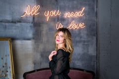 Young blonde woman smiling and looking on camera All you need is love neon sign on a background Royalty Free Stock Images