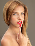 Young blonde woman smudging her lipstick Stock Images