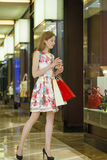 Young blonde woman with some shopping bags in the mall Royalty Free Stock Photography