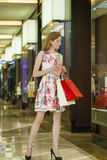 Young blonde woman with some shopping bags in the mall Royalty Free Stock Photos