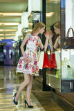 Young blonde woman with some shopping bags in the mall Stock Images