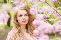 Young blonde woman standing in a blooming garden Royalty Free Stock Photography