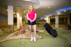 A young blonde woman standing in golf club near the black stick bag. Mid shot royalty free stock images