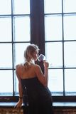 Young blonde woman standing in her apartment sipping a glass of red wine , side view at window Royalty Free Stock Image