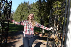 Young blonde woman standing at open gates. Pretty blonde woman standing at open wrought iron gate that leads into garden beyond Royalty Free Stock Image