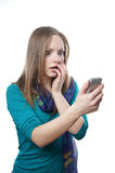 Shocked young woman. Young blonde woman staring at her mobile phone in disbelief stock images